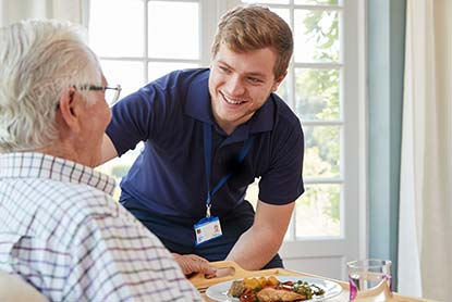 Carer giving food to patient